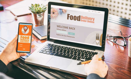 Food online order and delivery app on laptop and phone screens, man at work, business office background. Takeaway food order delivery service application 免版税图像