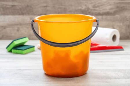 Cleaning bucket orange color on the floor, home interior wood floor background. Domestic household or business sanitary cleaning Zdjęcie Seryjne