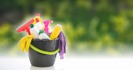 Cleaning products against blur green nature background. Chemical detergents in a bucket, spring home household concept, copy space