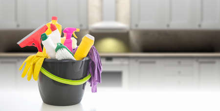 Cleaning products against blur kitchen interior background. Chemical detergents in a bucket, home kitchen household concept, copy space Фото со стока