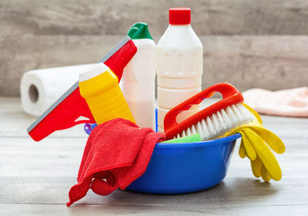 Cleaning products on the floor, home interior background. Chemical detergent bottles in a blue bowl. Domestic household or business sanitary cleaning