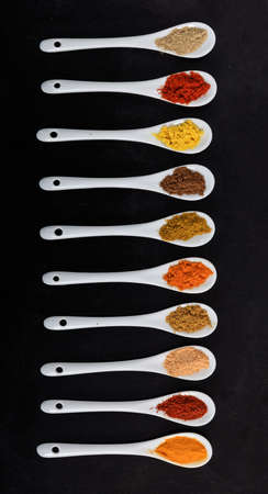 Spices powder variety in white porcelain spoons, black color background, top view. Cooking food seasoning Zdjęcie Seryjne