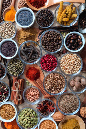Spices and herbs flat lay, wood table background, top view. Cooking food seasoning seeds