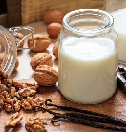 Walnut milk non dairy milk substitute on a wooden table. Nuts and glass with milk, lactose free milk substitute for vegans Zdjęcie Seryjne