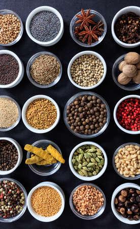Spices and herbs flat lay, black color background, top view. Cooking food seasoning seeds Zdjęcie Seryjne