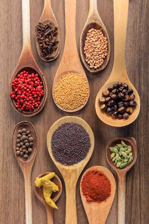 Spices and herbs seeds and ground flat lay, wood table background, top view. Cooking food seasoning
