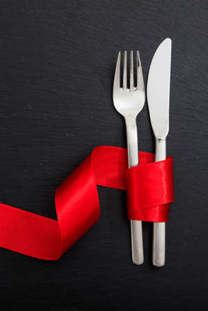 Valentine day dinner table setting. Fork and knife cutlery tied with passion red color ribbon on black background, top view.