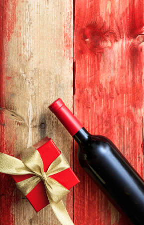 Valentines day concept. Red wine bottle and a gift on wood, top view