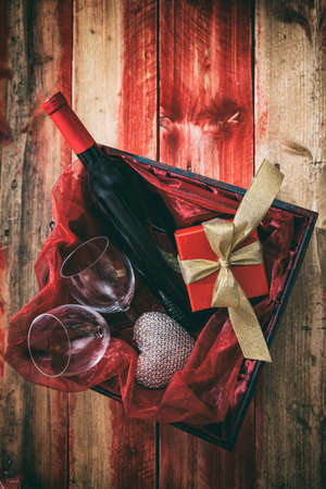 Valentines day concept. Red wine bottle, glasses in a gift box, top view