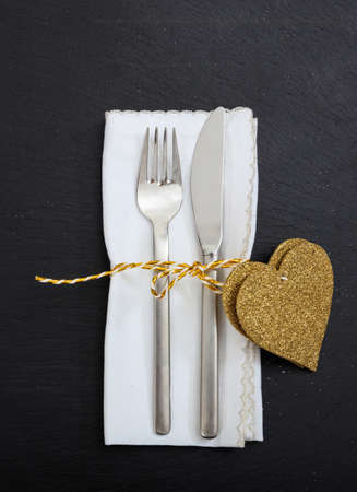 Valentine day dinner table setting. Fork and knife cutlery, white napkin and gold color hearts on black background, top view.