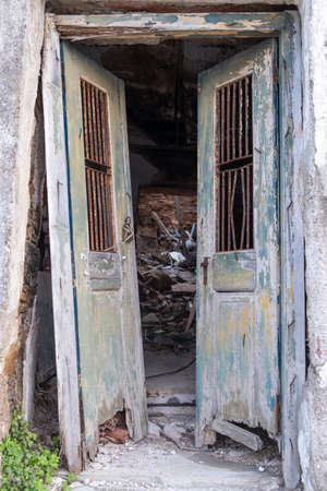 Old and destroyed double open door. Wooden, peeled, unlocked doorway in an abandoned and ruined house. Danger of collapse, vertical view.