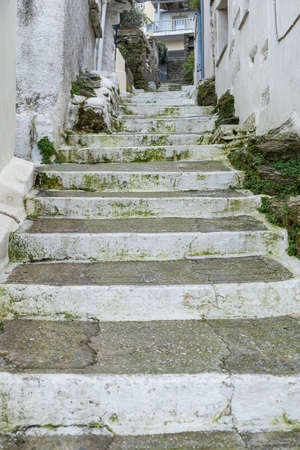 Greece, Tzia Kea island. Ioulis capital town narrow street with stairs and traditional stone walls, vertical view