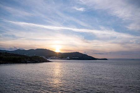 Sunset over Aegean sea, blue orange color sky with clouds background, Kea island, Korissia port, Greece. Zdjęcie Seryjne