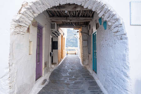 Traditional greek whitewashed buildings, cobblestone streets and stone structure arch in Ioulida village, Chora.