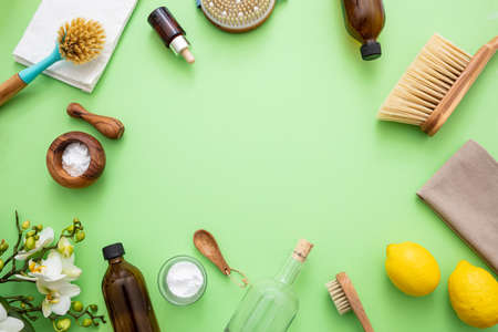 Eco cleaning household background. Cleaning products homemade safe non toxic flat lay, baking soda, lemon vinegar and fresh spring blossoms on green color background,