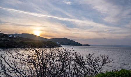 Sunset over Aegean sea, blue orange color sky with clouds background, Kea island, Gialiskari beach, Greece.