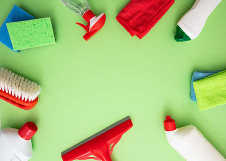 Household cleaning background. Cleaning products flat lay, chemical detergent bottles and equipment on green color background, Top view, copy space