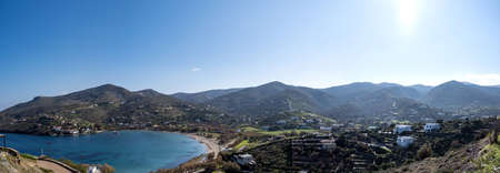 Tzia, Kea island, Greece. Aerial and panoramic view of Otzias bay. Houses next to the clear and calm blue sea under sunbeams. Panorama, banner. Zdjęcie Seryjne
