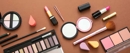 Makeup cosmetics products against brown color background. Make up female accessories, flat lay, top view, banner