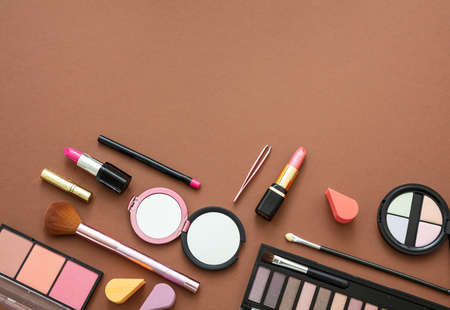 Makeup cosmetics products against brown color background. Make up female accessories, flat lay, top view, copy space Zdjęcie Seryjne