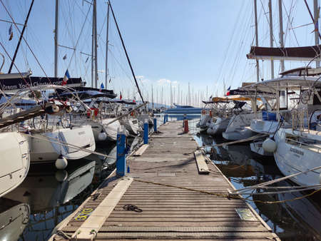 Athens, Greece. February 9, 2020. Wooden platform separate docked yachts with masts at Alimos Marina, the biggest marine in Balkans. Reflection of boats on blue calm sea, clear sky background. Editorial