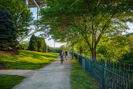 People riding bikes on a path, under green trees in spring. A place for relaxation and activities. Pittsburgh, Pennsylvania, USA.
