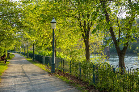 Young girl sitting on a bench on a path by the river under green trees, springtime. A place for relaxation and activities. Pittsburgh, Pennsylvania, USA. Zdjęcie Seryjne
