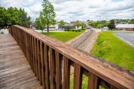 Footbridge crossing over railway, wooden pedestrian bridge closeup view, blur railroad and landscape, Oklahoma, US