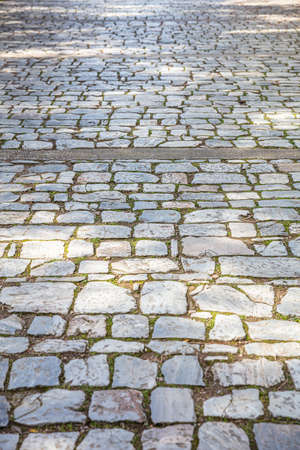 Old stone marble paved footpath, cobblestone pathway background, texture. Perspective high angle view Foto de archivo