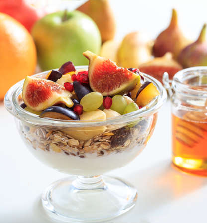 Breakfast healthy concept. Yoghurt, muesli and fresh fruits in a bowl, blur background. Closeup view of food for a healthy lifestyle.