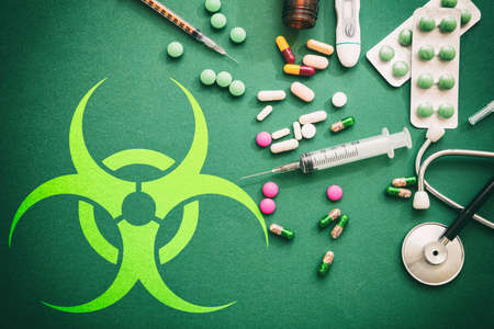Virus flat lay, therapy concept. Virus sign on green background with madicine and medical tools, top view