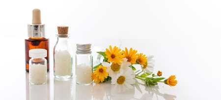 Alternative herbal medicine. Fresh wild flowers, homeopathic globules and essensial oil isolated against white background. Homeopathy, natural products concept