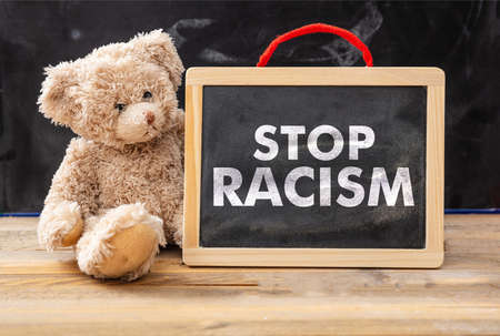 Stop racism and kids concept. Teddy bear and a board with Stop racism text, school class blackboard background. No to racism for children message.