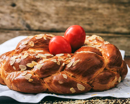 Easter traditional sweet bread, greek tsoureki and red eggs closeup view. Orthodox Christian Easter tradition