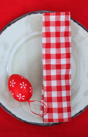 Easter table, place setting. Red eggs and napkin on a plate, red tablecloth, top view. Orthodox Christian Easter celebration table
