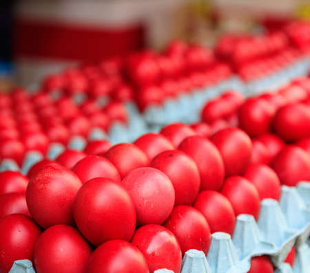 Red easter eggs for sale at an open-air market close up view. Easter orthodox christian holiday tradition Stock Photo