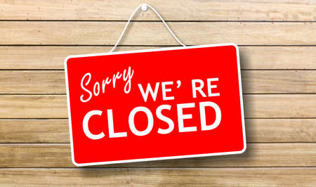 Closed business or store concept. Red color sign board, Sorry we re closed text hanging on store wooden door background,