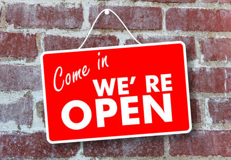 Open come in store sign. Red color sign board, Come in we re open text hanging on brick wall background Stockfoto