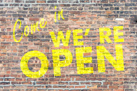 Open come in store sign. Yellow color text Come in we re open on brick wall background. Wellcome sign to inform the customers about the business operation Banco de Imagens
