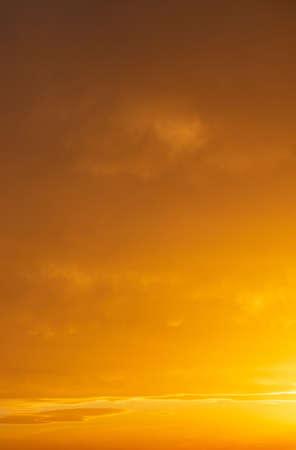 Sunset sky. Sunrise paints with orange shades the cloudy sky background.