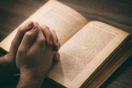 Prayer, man hands over an open book Holy Bible, wooden desk background. Faith, religion and spirituality concept Reklamní fotografie