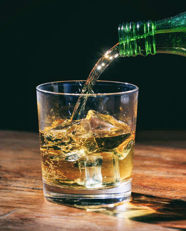 Green bottle pouring whiskey on the rocks, in crystal glass on wooden table. Vertical portrait of alcohol drink with ice cubes on dark background.