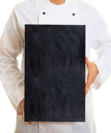 Restaurant menu blank black board. Chef with white uniform, holds an empty menu board, standing on white background. Copy space, vertical portrait.