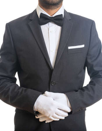 Butler, waiter with blue black color tuxedo and bow tie, folded hands with gloves, ready to serve, standing on white background. Vertical portrait. Archivio Fotografico
