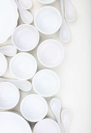 Dishware concept. White empty porcelain bowls and teaspoons background. Clean, new, luxury soup pots and spoons, vertical photo. Banque d'images