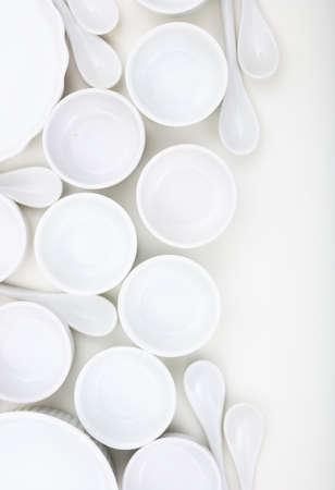Notion de vaisselle. Fond de bols et cuillères à café en porcelaine vide blanc. Pots à soupe et cuillères propres, neufs et de luxe, photo verticale. Banque d'images