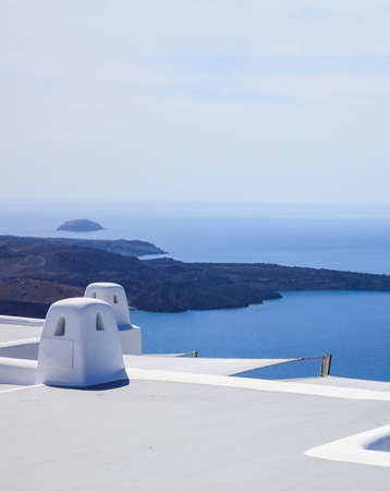 Santorini island, Greece, White terrace and traditional chimney on caldera overlooking the sea. White architecture against blue sea and clear sky background, vertical photo