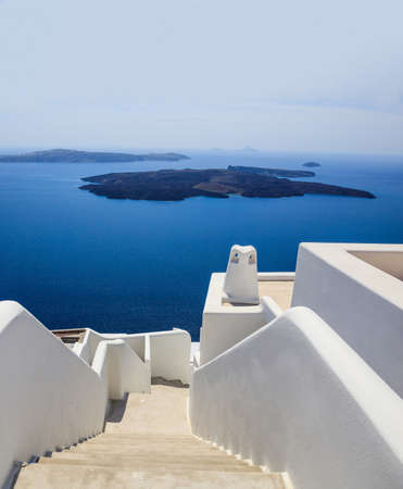 Santorini island, Greece, White traditional architecture in caldera, stairs and building details against blue sea and clear sky background, vertical photo