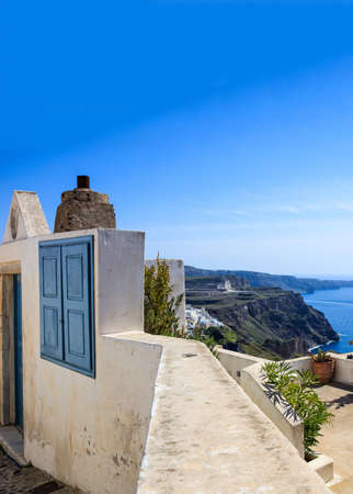 Santorini island, Greece. Traditional architecture, house entrance, terrace and caldera view over Aegean sea, blue clear sky, calm sea 免版税图像