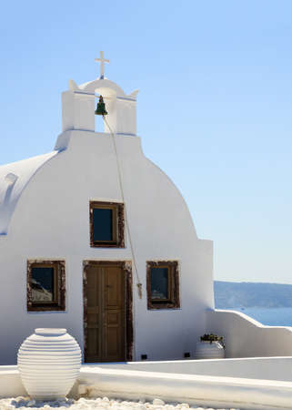 Santorini island, Greece. White orthodox church and bells, entrance front view, against blue sea and clear sky background, Oia village, vertical photo